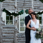 Fabric and magnolia backdrop on an old log cabin wall at La Lune Weddings & Events