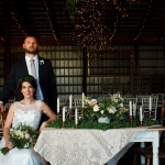 Couple with their sweetheart table at La Lune Weddings & Events