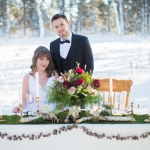 Winter bride and groom at sweet heart table in the snow